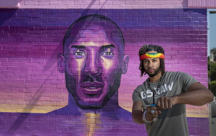 "Artist Joshua ""Prophet Josh"" McCadney, a.k.a. @paintedprophet, stands by one of two Kobe tribute murals he created on Melrose Avenue within two weeks of Kobe Bryant's death. <span class=""copyright"">(Allen J. Schaben / Los Angeles Times)</span>"