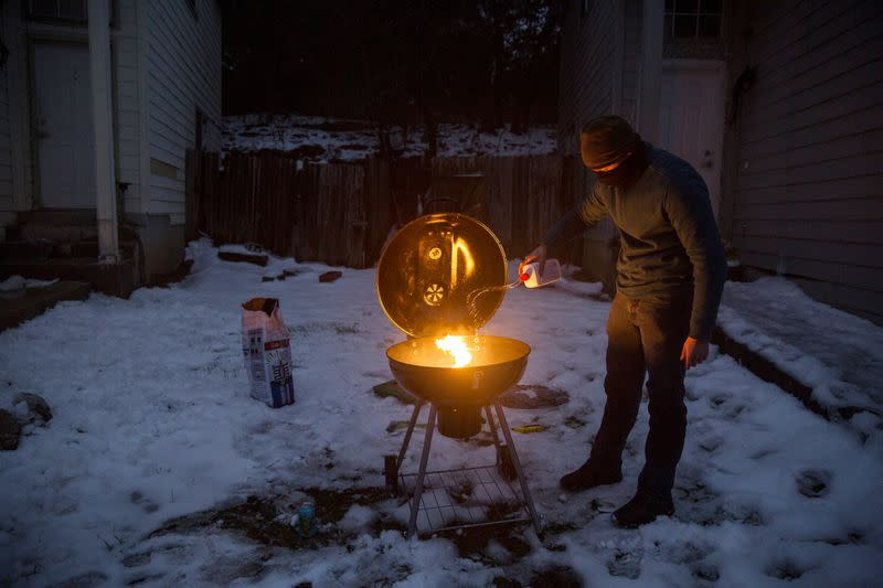 Max King cooks a pizza on a charcoal grill after winter weather caused electricity blackouts in San Marcos