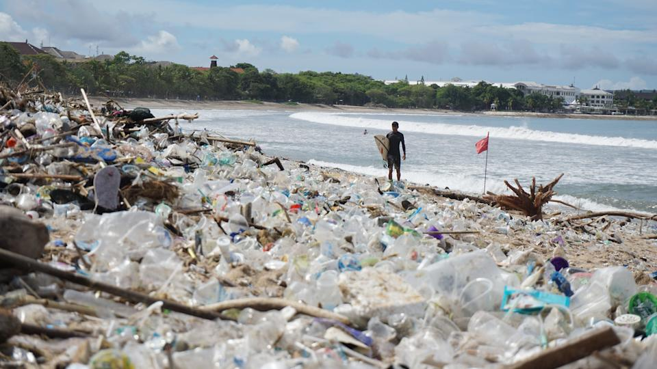 A surfer stands on the sand where a huge amount of plastic bottles and other rubbish sits on a Bali beach.