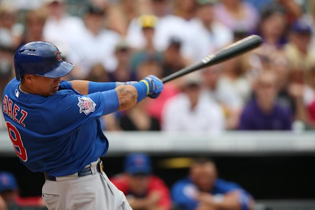 Chicago Cubs' Javier Baez extends his swing after connecting for a solo home run to lead off the sixth inning of the Cubs' 6-2 victory over the Colorado Rockies in a baseball game in Denver on Thursday, Aug. 7, 2014. (AP Photo/David Zalubowski)