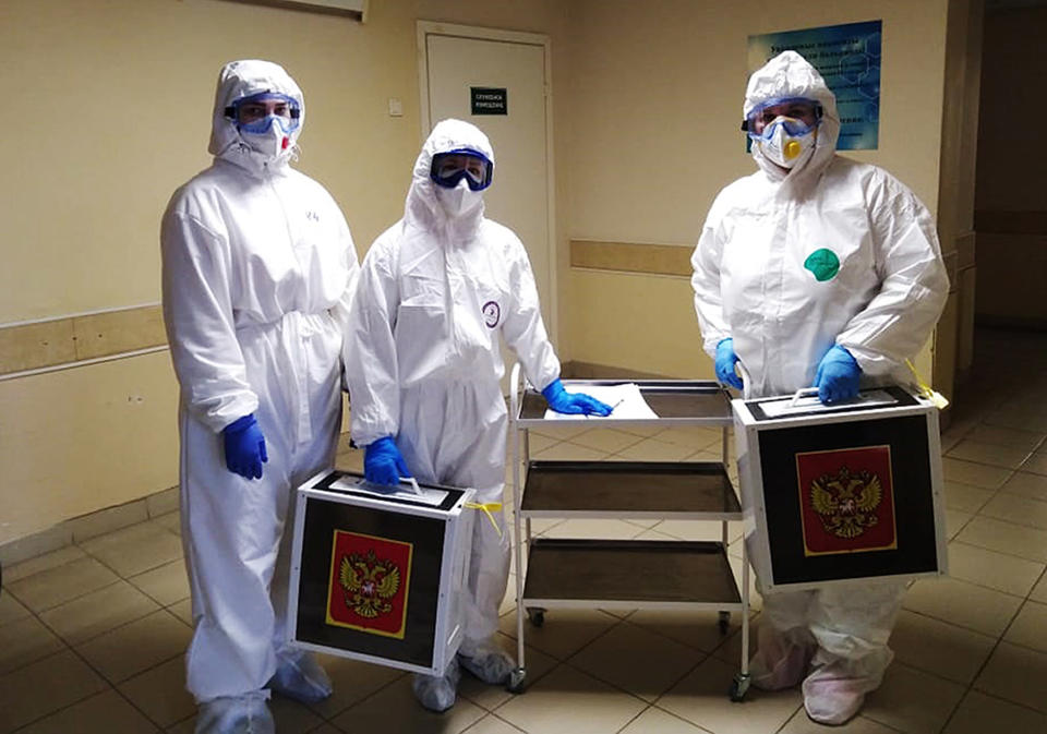 Medical workers wearing protective gear hold ballot boxes pose for a photo prior to go into the red zone to help to coronavirus patients to attend the voting during the Parliamentary elections in Voronezh, Russia, Sunday, Sept. 19, 2021. From the Baltic Sea to the Pacific Ocean, Russians across eleven time zones voted Sunday on the third and final day of a national election for a new parliament, a ballot in which the pro-Kremlin ruling party is largely expected to retain its majority after months of relentless crackdown on the opposition. (AP Photo)
