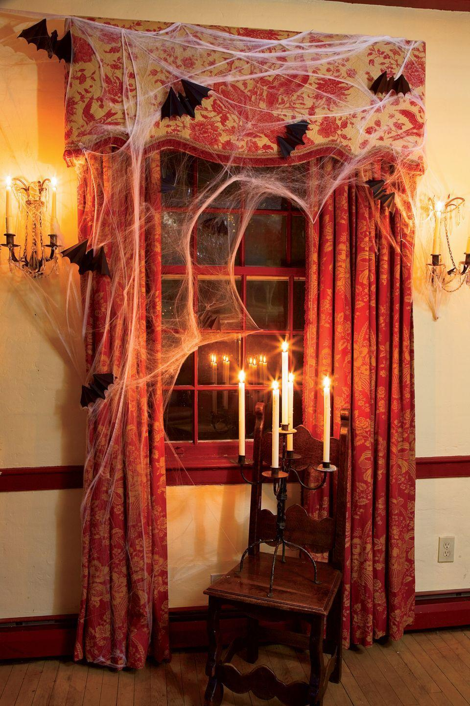 """<p>Use candlelight to create dark shadows in the corners. Here, ghostly white tapers in a flea market <span class=""""redactor-unlink"""">candelabra</span> enhance the creepiness of cobwebs and flying bats. </p>"""