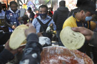 A devotee wearing a protective face mask amid the new coronavirus pandemic and carrying his Saint Jude statue, watches vendors prepare tacos during the annual pilgrimage honoring Jude, the patron saint of lost causes, in Mexico City, Wednesday, Oct. 28, 2020. Thousands of Mexicans did not miss this year to mark St. Jude's feast day, but the pandemic caused Masses to be canceled and the rivers of people of other years were replaced by orderly lines of masked worshipers waiting their turn for a blessing. (AP Photo/Marco Ugarte)