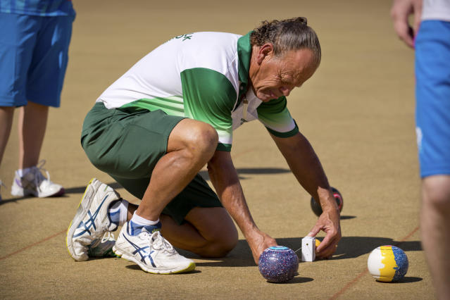 Second Hadyn Evans of Norfolk Island measures during their men's triples semifinal lawn bowling match against Scotland at the Broadbeach Bowls Club during the 2018 Commonwealth Games on the Gold Coast, Australia, Sunday, April 8, 2018. The Norfolk team won the bronze medal with a 19-16 victory over Canada, securing the islands second medal ever at the Commonwealth Games. (AP Photo/Mark Schiefelbein)