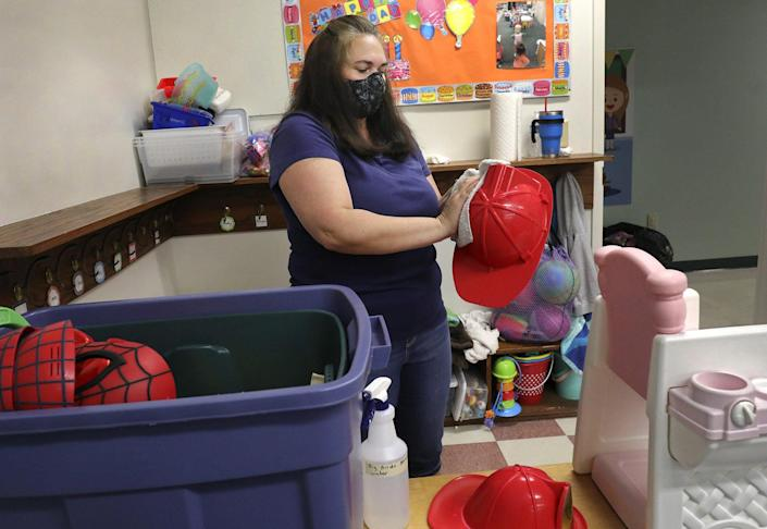 Preschool teacher Juila Teets cleans toys at the Play and Learn Christian Child Care Center in Clintonville on Thursday in preparation for the center's reopening. It will serve 30 fewer kids to stay under limits on class sizes and caregiver-to-child ratios.