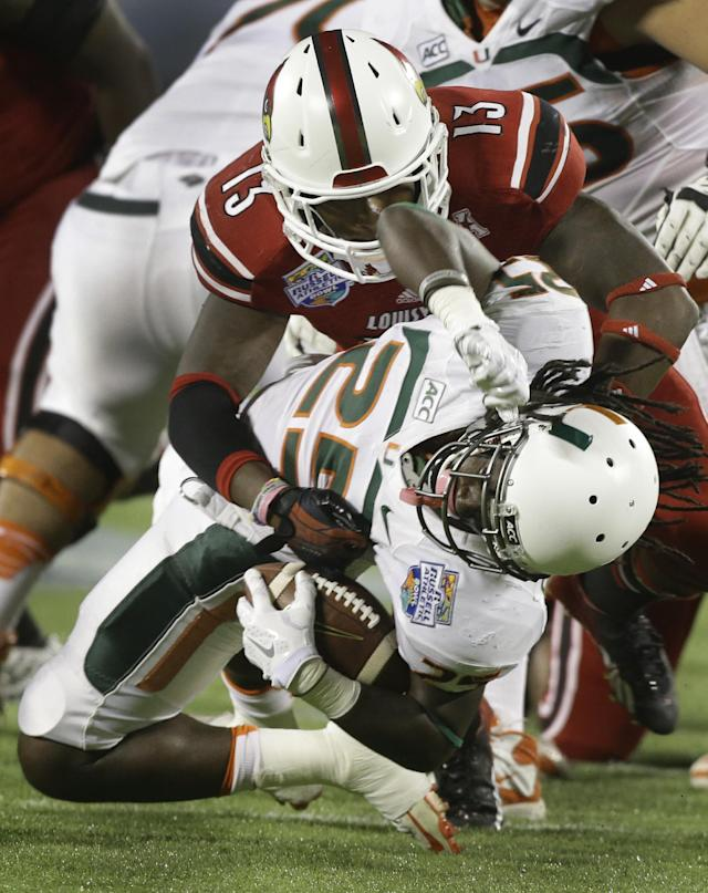 Louisville linebacker James Burgess (13) stops Miami running back Dallas Crawford (25) for a 5-yard loss during the first half of the Russell Athletic Bowl NCAA college football game in Orlando, Fla., Saturday, Dec. 28, 2013. (AP Photo/John Raoux)