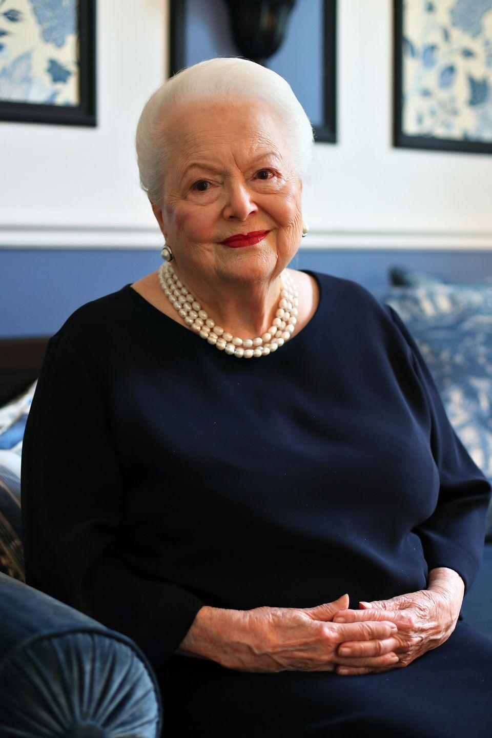 <p>At 100, de Havilland smiles in a classic navy dress and pearl jewelry. </p>