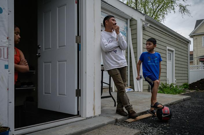 Valeriano (C), 34, an undocumented Guatemalan farmer who entered the US illegally at the end of March 2021 after being deported following his first attempt, stands at the entrance to the basement home he shares with his son Arnold (R) and his niece (L) in Hartford, Connecticut on April 29, 2021. / Credit: ED JONES/AFP via Getty Images