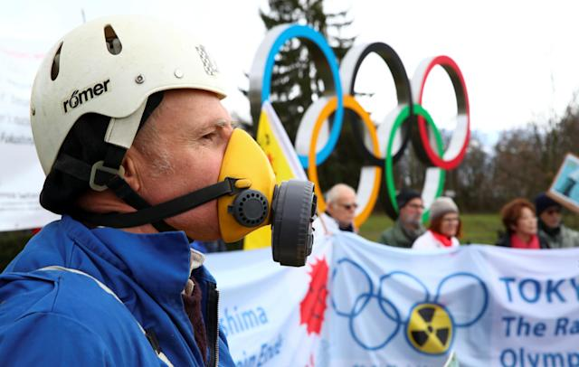 A man wearing a mask takes part in a protest against the holding of the 2020 Olympic Games in Tokyo under the state of nuclear emergency, in front of the International Olympic Games (IOC) in Lausanne, Switzerland. (Reuters)