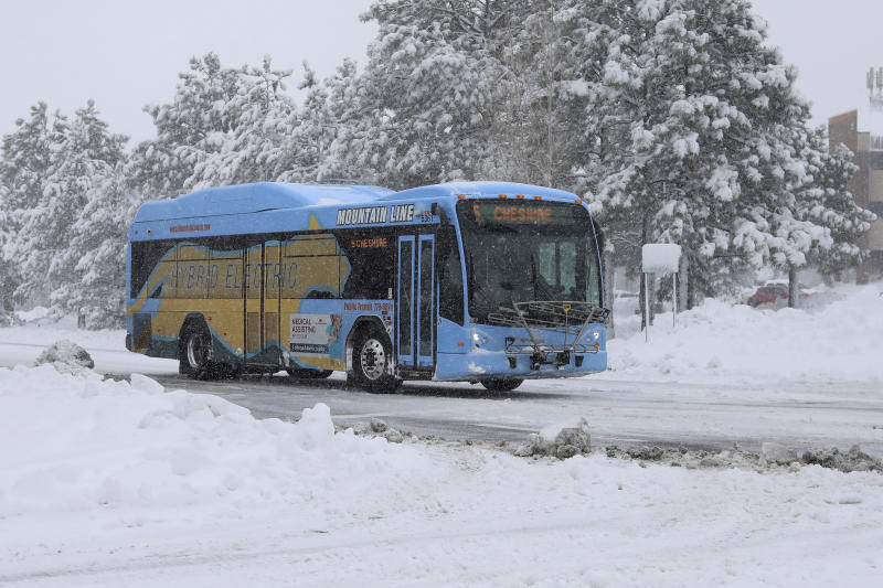 A bus from the Northern Arizona Intergovernmental Public Transportation Authority (NAIPTA) turns toward downtowndowntown Flagstaff, Ariz., Friday, Nov. 29, 2019. A powerful storm making its way east from California is threatening major disruptions during the year's busiest travel weekend, as forecasters warned that intensifying snow and ice could thwart millions across the country hoping to get home after Thanksgiving. . (Cody Bashore/Arizona Daily Sun via AP)