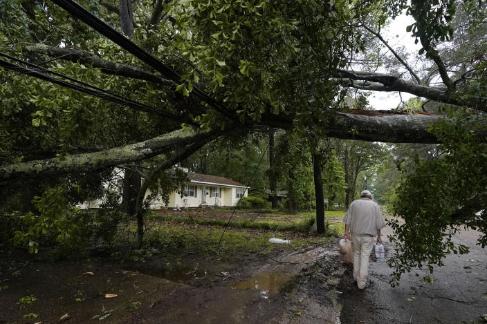 A northeast Jackson, Miss., resident walks past a wind toppled tree in his neighborhood, Tuesday afternoon, May 4, 2021. The severe weather was not unexpected, since the state was hit with a number of tornadoes on Sunday. (AP Photo/Rogelio V. Solis)