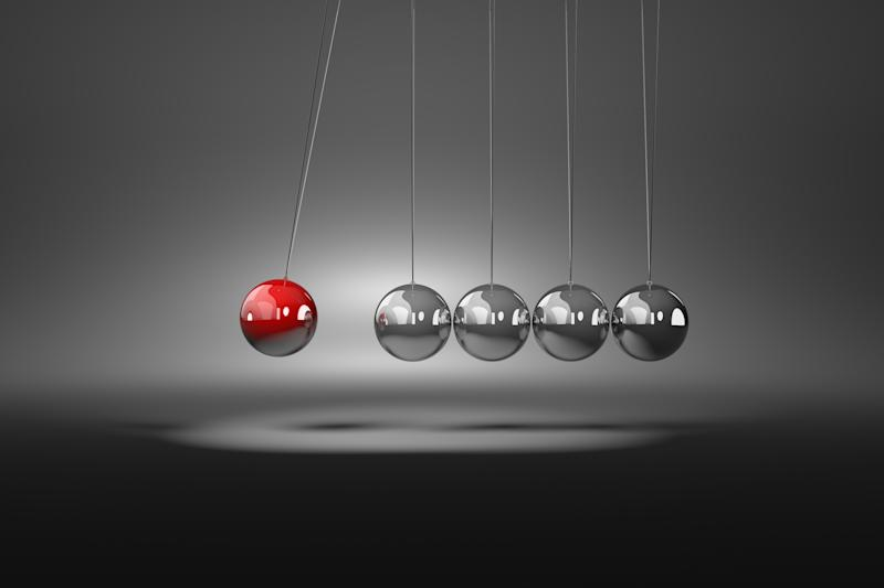 A red metallic ball on a string moving towards a series of four grayish metallic balls that are also attached to strings.