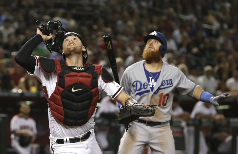 Arizona Diamondbacks catcher Carson Kelly, left, and Los Angeles Dodgers' Justin Turner (10) look up on a wild pitch by Diamondbacks relief pitcher Yoshihisa Hirano as the ball gets past everyone during the seventh inning of a baseball game, Monday, June 24, 2019, in Phoenix. (AP Photo/Ross D. Franklin)