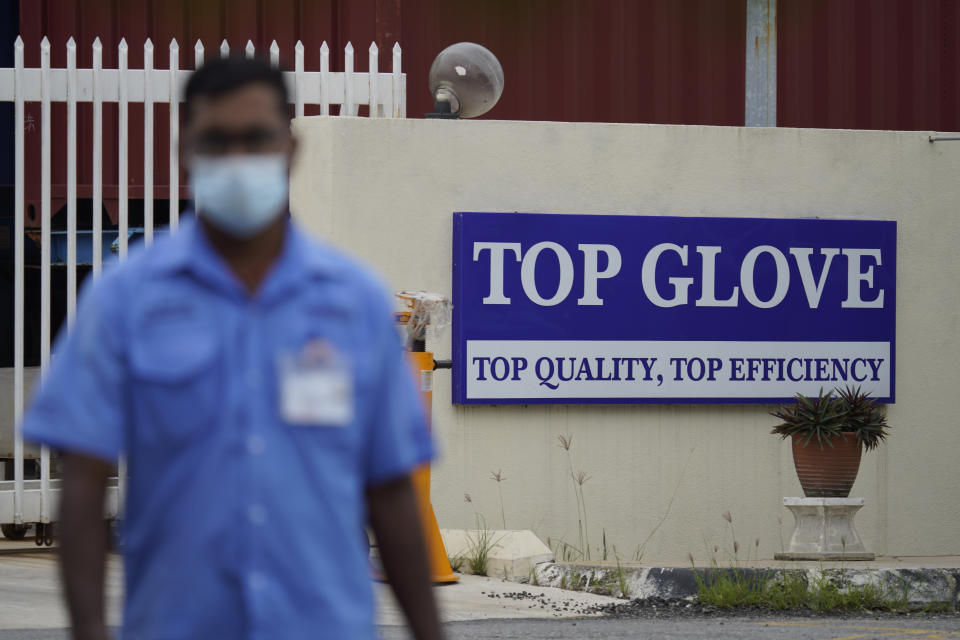 A worker from Top Glove walks outside Top Glove factory in Shah Alam, Malaysia, Wednesday, Nov. 25, 2020. Malaysia's Top Glove Corp., the world's largest maker of rubber gloves, says it expects a two to four-week delay in deliveries after more than 2,000 workers at its factories were infected by the coronavirus, raising the possibility of supply disruptions during the pandemic. (AP Photo/Vincent Thian)