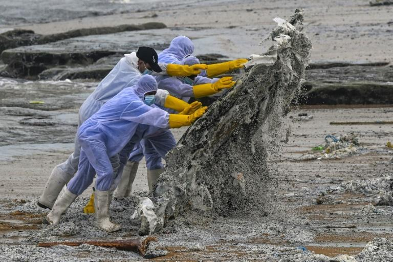 Navy personnel remove debris washed ashore from the Singapore-registered container ship MV X-Press Pearl, which is on fire off the coast of Sri Lanka