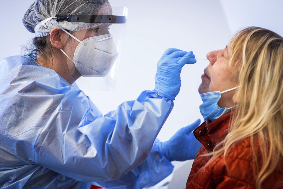 Susann Zierenner, left, of the German Red Cross takes a test with a test stick from resident Angelika Dankert after the opening of the municipal Corona test centre in Ludwigslust, Germany, Monday, March 15, 2021. At the centre, residents can have themselves tested for possible infection with the Corona virus using a free rapid test. (Jens Buettner/dpa via AP)