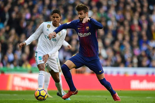 "Barcelona defender Gerard Pique (R) escapes a tackle by Real Madrid defender Raphael Varane during the Spanish League ""El Clasico"" at the Santiago Bernabeu stadium in Madrid on December 23, 2017 (AFP Photo/Javier SORIANO)"