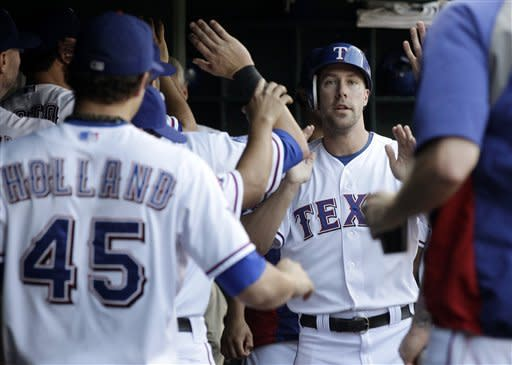 Texas Rangers' David Murphy is congratulated in the dugout after scoring on a Mitch Moreland single in the second inning of a baseball game against the Minnesota Twins on Friday, Aug. 24, 2012, in Arlington, Texas. (AP Photo/Tony Gutierrez)