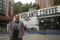 Chris Vigilante poses in front of one of his coffee shops, Wednesday, Sept. 1, 2021, in College Park, Md. A confluence of supply chain problems, drought, frost and inflation all point to the price of your cup of morning coffee going up. The tricky part is trying to figure when — and how much. (AP Photo/Julio Cortez)