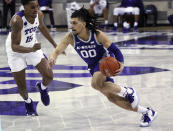 TCU forward Terren Frank (15) defends as Kansas State guard Mike McGuirl (0) drives during the second half of an NCAA college basketball game Saturday, Feb. 20, 2021, in Fort Worth, Texas. (AP Photo/Richard W. Rodriguez)