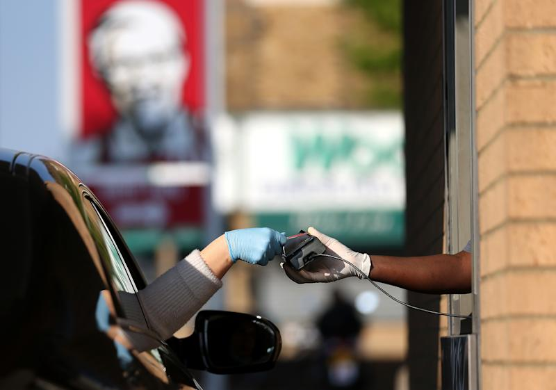 LONDON, UNITED KINGDOM - MAY 04: A worker takes a payment from a customer at KFC as it re-opens for Drive-Thru at a branch in Leyton on May 04, 2020 in London, United Kingdom. The country continued quarantine measures intended to curb the spread of Covid-19, but the infection rate is falling, and government officials are discussing the terms under which it would ease the lockdown. (Photo by Alex Pantling/Getty Images)