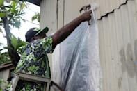 A resident of Fiji's capital Suva prepares his home for the arrival of super Cyclone Yasa