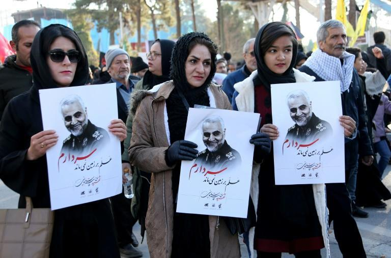 Iranian mourners hold posters of slain top general Qasem Soleimani during the final stage of funeral processions in his hometown Kerman