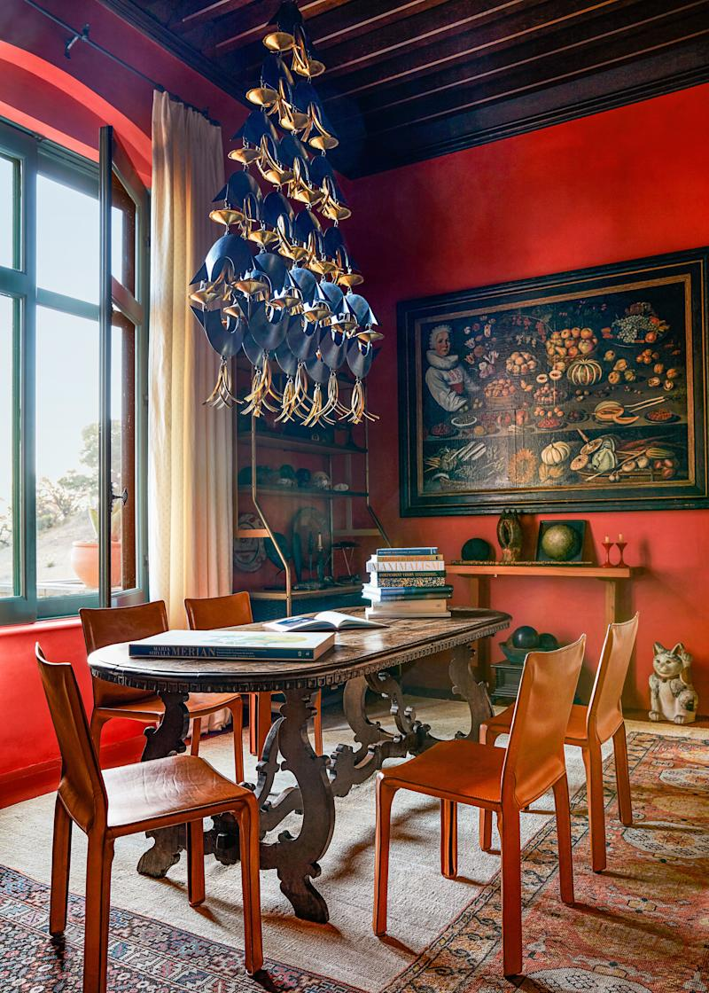 A paprika red paints the dining room walls. Sam Orlando Miller designed the hanging candelabra; vintage Mario Bellini cab chairs.