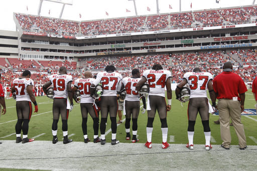 Members of the Tampa Bay Buccaneers observe a moment of silence for former NFL owner Art Modell prior to the game against the Carolina Panthers. The Buccaneers defeated the Panthers 16-10 in an NFL game on Sunday, Sept. 9, 2012, in Tampa, Fla. (AP Photo/Margaret Bowles)