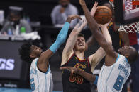 Cleveland Cavaliers center Isaiah Hartenstein, center, shoots between Charlotte Hornets forward Jalen McDaniels, left, and center Bismack Biyombo (8) during the second quarter of an NBA basketball game in Charlotte, N.C., Wednesday, April 14, 2021. (AP Photo/Nell Redmond)