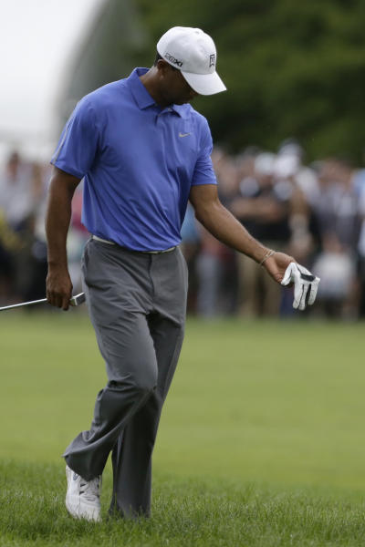 Tiger Woods looks at his wrist after a shot on the first hole during the first round of the U.S. Open golf tournament at Merion Golf Club, Thursday, June 13, 2013, in Ardmore, Pa. (AP Photo/Gene J. Puskar)
