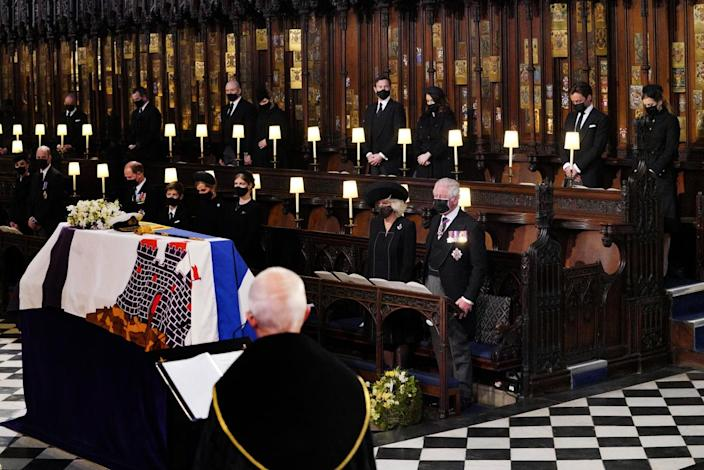 Royal family members are spaced apart in small groups in St. George's Chapel near Prince Philip's coffin.