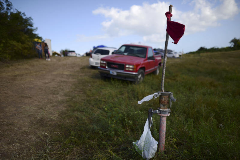 In this Friday, Jan. 10 photo, a red flag marks the entrance to a private hay farm where residents from the Indios neighborhood of Guayanilla, Puerto Rico are setting up shelter after earthquakes and continuing aftershocks in Guayanilla, Puerto Rico. A 6.4 magnitude quake that toppled or damaged hundreds of homes in southwestern Puerto Rico is raising concerns about where displaced families will live, while the island still struggles to rebuild from Hurricane Maria two years ago. (AP Photo/Carlos Giusti)