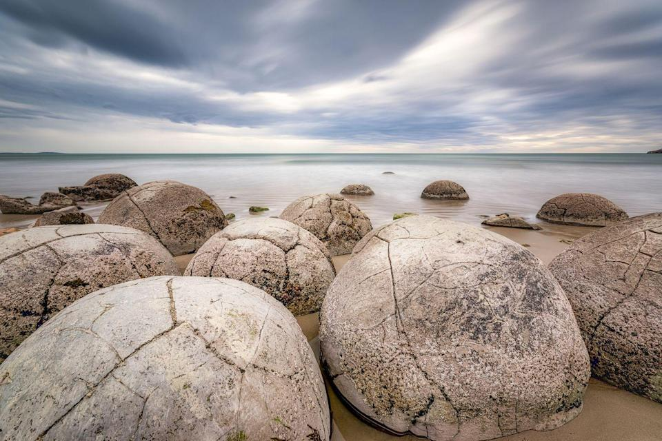 """<p>Home to almost perfectly spherical boulders, this beach resembles a carton full of stone eggs. Formed roughly <a href=""""https://www.newzealand.com/us/feature/moeraki-boulders/"""" rel=""""nofollow noopener"""" target=""""_blank"""" data-ylk=""""slk:65 million"""" class=""""link rapid-noclick-resp"""">65 million</a> years ago, these calcite boulders are legendary. No, really, they're central to a Maori legend of a disastrous canoe voyage. </p>"""