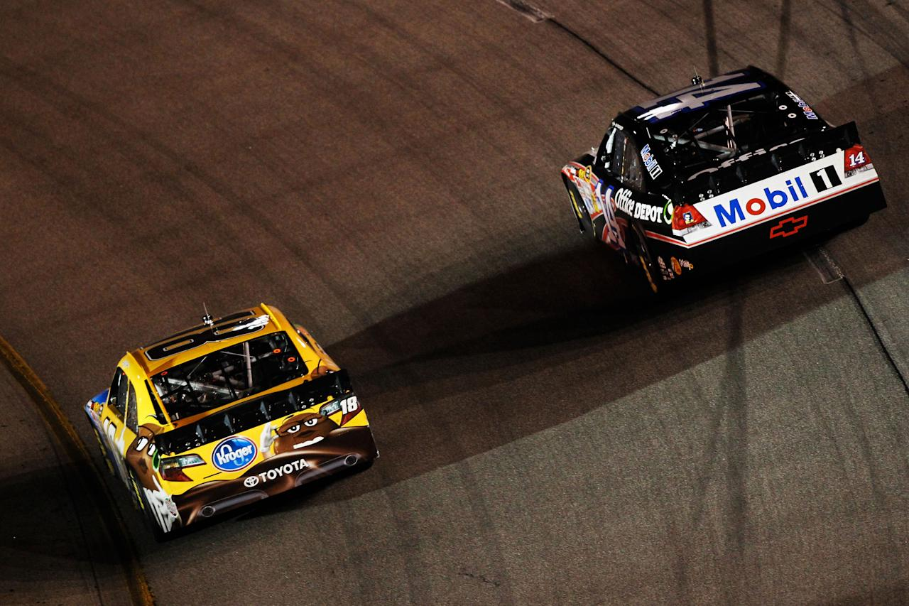 RICHMOND, VA - APRIL 28:  Kyle Busch, driver of the #18 M&M's Ms. Brown Toyota, races Tony Stewart, driver of the #14 Mobil 1/Office Depot Chevrolet, side by side during the NASCAR Sprint Cup Series Capital City 400 at Richmond International Raceway on April 28, 2012 in Richmond, Virginia.  (Photo by Todd Warshaw/Getty Images for NASCAR)