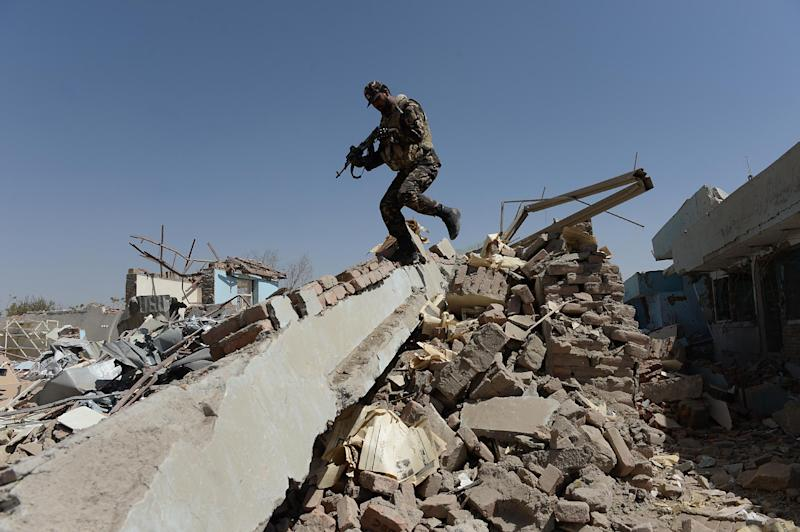 An Afghan soldier walks over rubble at the scene of a suicide attack on a government compound in Ghazni earlier this month (AFP Photo/Shah Marai)