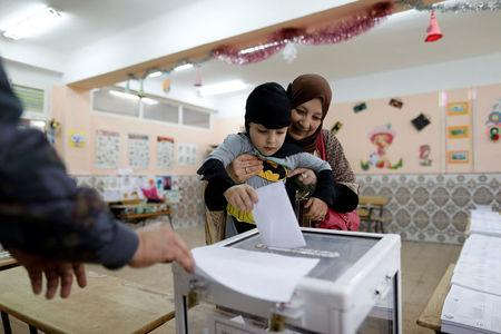 A woman carries her son to cast her vote at a polling station during the parliamentary election in Algiers