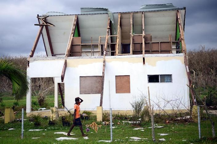 A boy walks past a house badly damaged by Cyclone Pam on the Vanuatu island of Tanna on March 18, 2015 (AFP Photo/Jeremy Piper)