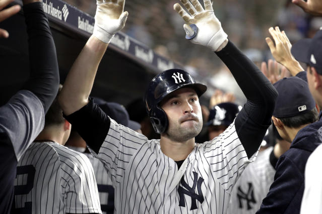 New York Yankees' Neil Walker is congratulated by teammates after hitting a three-run home run off Boston Red Sox relief pitcher Ryan Brasier during the seventh inning of a baseball game Tuesday, Sept. 18, 2018, in New York. (AP Photo/Julio Cortez)