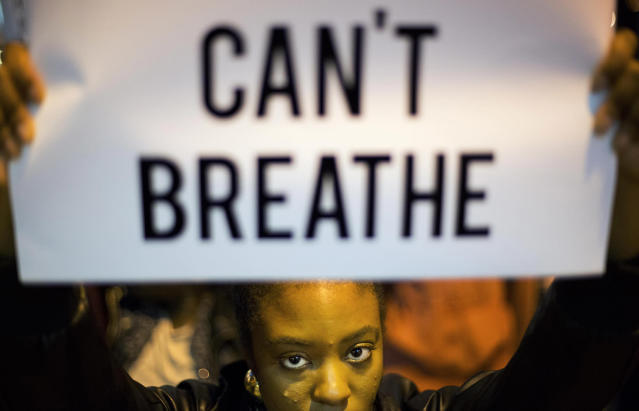<p>Atiya Elliott-Semper, of Atlanta, holds up a sign during a demonstration in Atlanta on Dec. 4, 2014 against the deaths of two unarmed black men at the hands of white police officers in New York City and Ferguson, Mo. (AP Photo/David Goldman) </p>