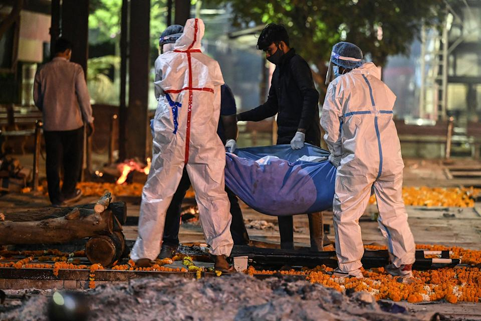 <p>Relatives and family members carry the dead body of a Covid-19 victim for a cremation  in New Delhi</p> (Getty Images)