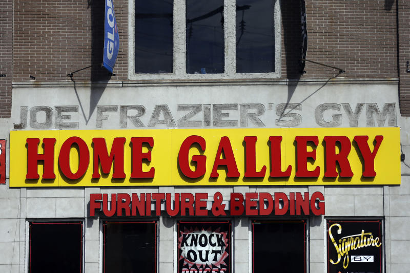 The façade of a furniture store is over the original sign for the gym where heavyweight champ Joe Frazier lived and trained, on Tuesday, April 30, 2013, in Philadelphia. The building has been named to the National Register of Historic Places. (AP Photo/Matt Rourke)