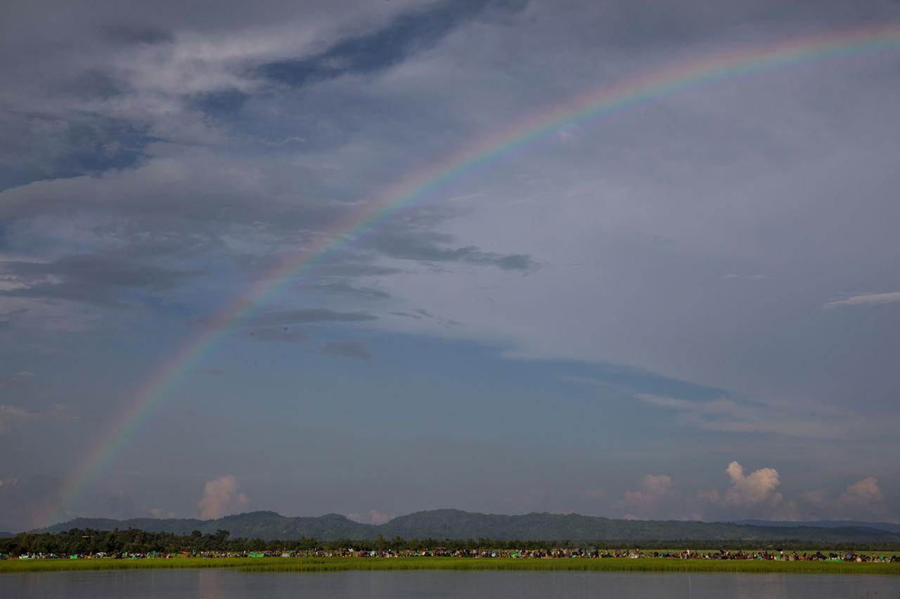 <p>A rainbow hovers above thousands of Rohingya refugees fleeing from Myanmar are kept under a tight security by Bangladeshi military after crossing the border in a rice paddy field near Palang Khali, Cox's Bazar, Bangladesh, on October 16, 2017. A rainbow appeared after a brief rainstorm. (Photograph by Paula Bronstein/Getty Images) </p>
