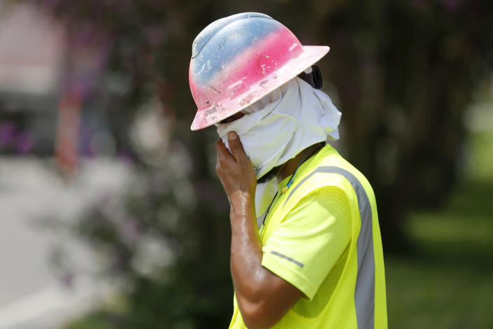 Construction worker Dineose Vargas wipes his face at a construction site on the Duncan Canal in Kenner, La., Tuesday, Aug. 13, 2019. Forecasters say most of the South, from Texas to parts of South Carolina, will be under heat advisories and warnings as temperatures will feel as high as 117 degrees. (AP Photo/Gerald Herbert)