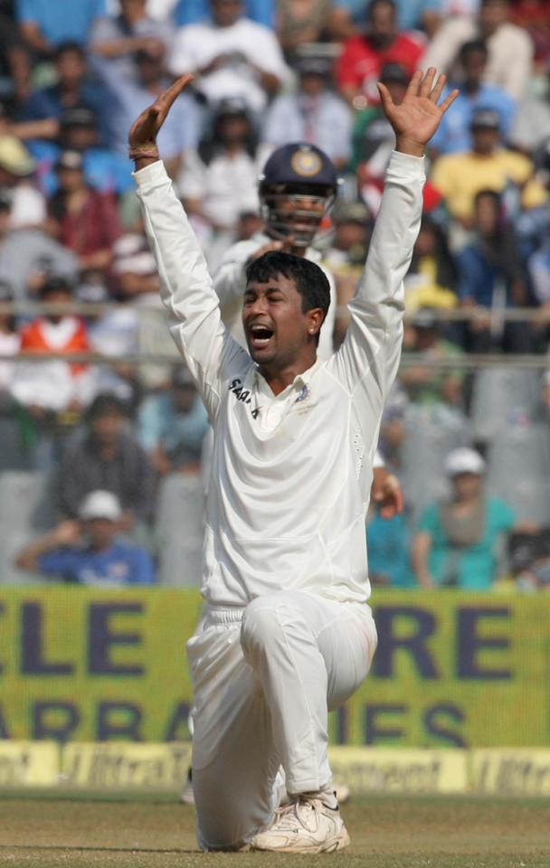 Indian cricketer Pragyan Ojha celebrates fall of a wicket during the 3rd day of the 2nd Test Match between India and West Indies at Wankhede Stadium in Mumbai on Nov.16, 2013. (Photo: IANS)