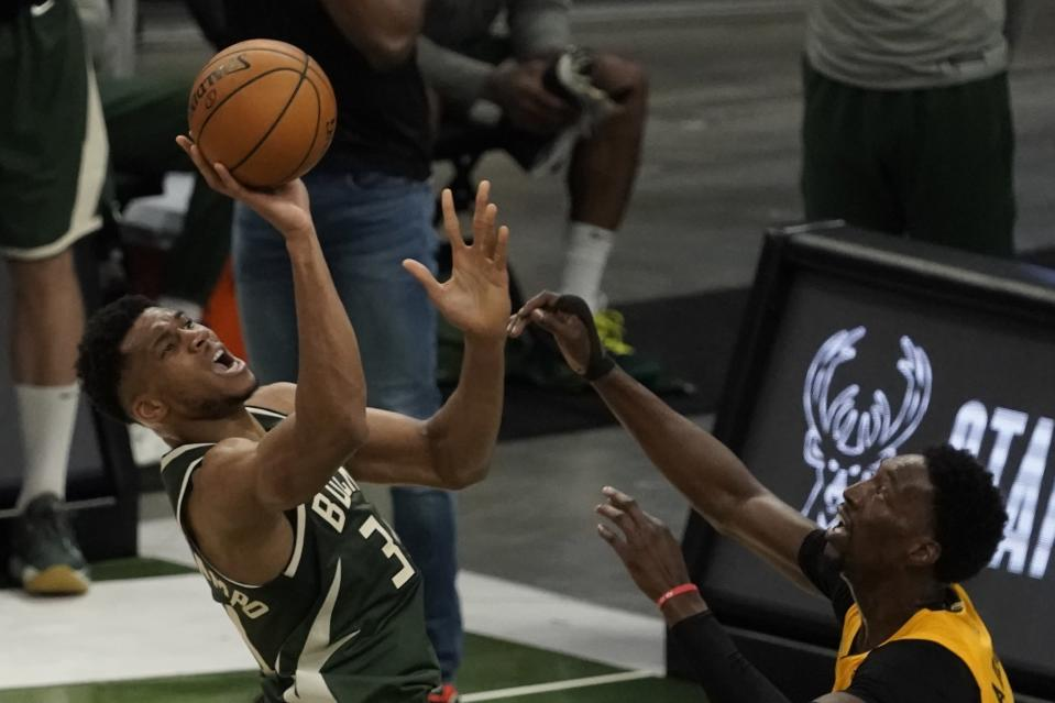Milwaukee Bucks' Giannis Antetokounmpo shoots over Miami Heat's Bam Adebayo during the first half of Game 1 of their NBA basketball first-round playoff series Saturday, May 22, 2021, in Milwaukee. (AP Photo/Morry Gash)
