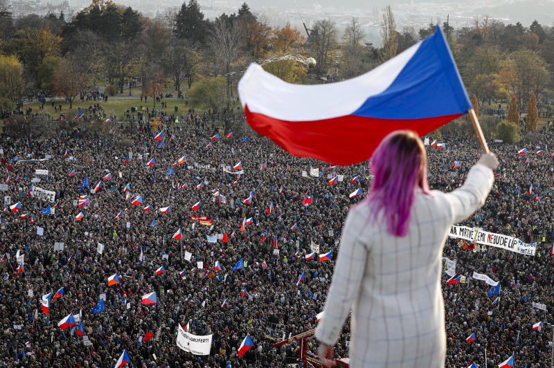 A woman waves a Czech flag from a roof as people take part in a large anti-government protest in Prague, Czech Republic, Saturday, Nov. 16, 2019. Czechs are rallying in big numbers to use the 30th anniversary of the pro-democratic Velvet Revolution and urge Prime Minister Andrej Babis to resign as peaceful protesters from all corners of the Czech Republic are attending the second massive protest opposing Babis at Letna park, a site of massive gatherings that significantly contributed to the fall of communism in 1989. (AP Photo/Petr David Josek)