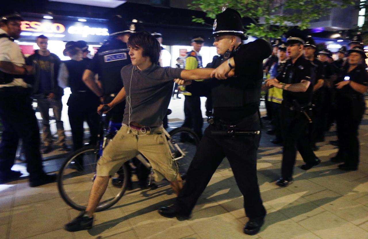 An officer arrests a cyclist after a Critical Mass bike protest outside the Olympic Park during the 2012 Summer Olympics Opening Ceremony, Friday, July 27, 2012, in London. (AP Photo/Matt Rourke)