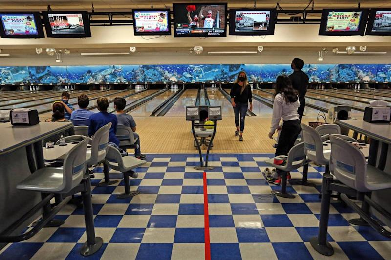 People enjoy bowling as they practice social distancing by leaving an empty lane at Bird Bowl Bowling Center on 9275 SW 40th St. in Westchester, Florida, as Miami-Dade County enters Phase 2 of reopening, Saturday, September 19, 2020.