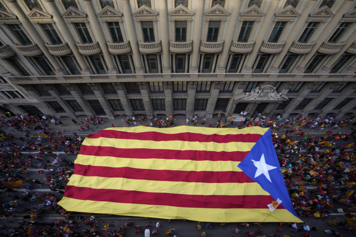 Demonstrators march holding a pro-independence flag during the Catalan National Day in Barcelona, Spain, Saturday, Sept. 11, 2021. Thousands of Catalans have rallied for independence from the rest of Spain in their first major mass gathering since the start of the pandemic. The march in Barcelona on Saturday comes before a meeting between regional leaders in northeast Catalonia and the Spanish government. ( AP Photo/Joan Mateu Parra)